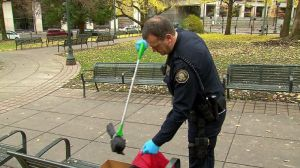 Officer cleaning up one of the many dead crows found in Portland's Waterfront Park.  Photo c/o KOIN 6 News